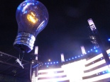An acrobat suspended ober the crowd by a lightbulb balloon in Estadi Olimpic in Barcelona. Image from musenewses.wordpress.com. 2013.